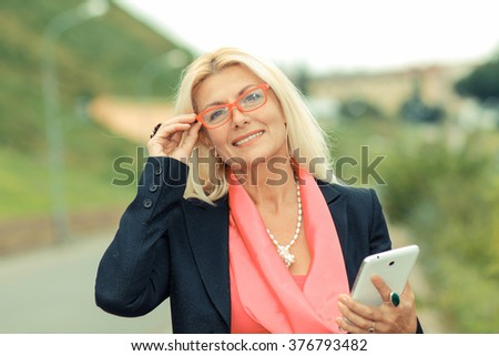 portrait of senior business woman with the tablet outdoors