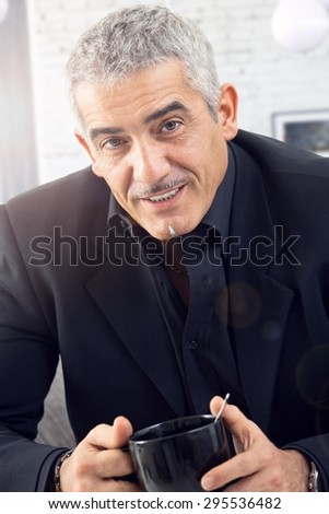 Portrait of senior businessman drinking tea, looking at camera.