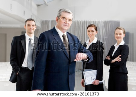 Portrait of senior businessman looking at camera while watching the time at background of confident managers - stock photo