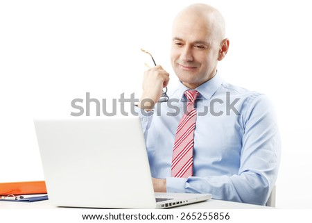 Portrait of senior businessman sitting at desk in front of his laptop ant thinking to solve the problem. Isolated on white background.  - stock photo