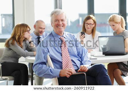Portrait of senior businessman sitting at meeting while business team working at background.  - stock photo