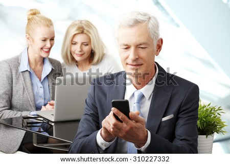 Portrait of senior businessman sitting at office while using his mobile and businesswomen working at background at laptop. Teamwork at office.  - stock photo