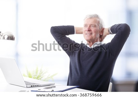 Portrait of senior businessman sitting in front of laptop and leaning back after successful project.   - stock photo