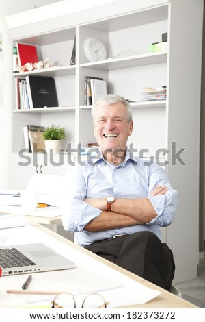 Portrait of senior businessman working in small architect studio.  - stock photo