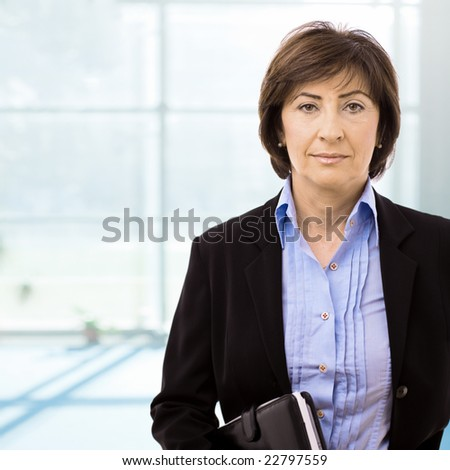 Portrait of senior businesswoman at office lobby. - stock photo