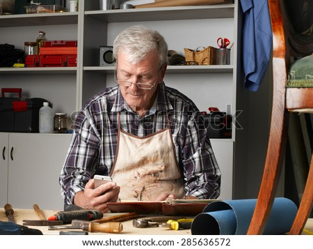 Portrait of senior carpenter working at his workshop while sitting at desk and reading message on mobile  - stock photo