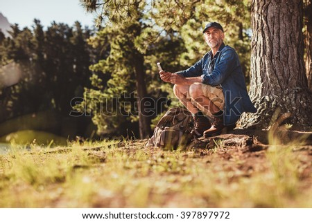 Portrait of senior caucasian man sitting outdoors in forest with a compass. Mature man hiking in nature looking for directions on a summer day. - stock photo