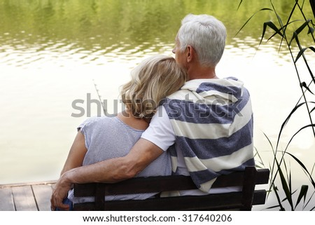 Portrait of senior couple chilling out at lakeside while sitting at the pier.  - stock photo