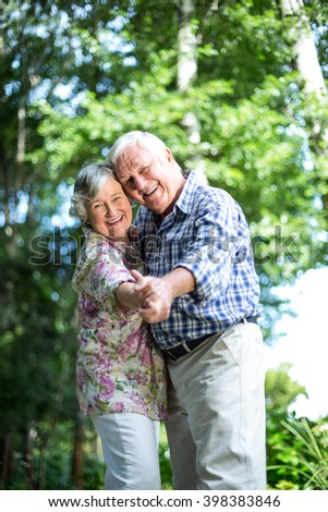 Portrait of senior couple dancing against trees in back yard - stock photo
