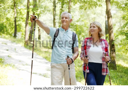 Portrait of senior couple enjoying a nordic walk. Active elderly woman and man walking on the forest and smiling. - stock photo