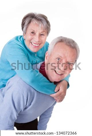 Portrait Of Senior Couple Enjoying Piggyback Isolated On White Background - stock photo
