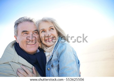 Portrait of senior couple having fun at the beach, wintertime
