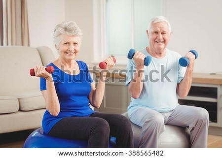 Portrait of senior couple lifting dumbbells while sitting on exercise ball at home