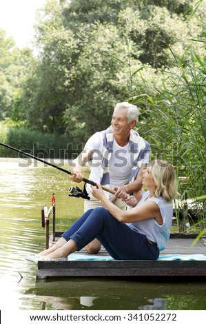 Portrait of senior couple relaxing at lakeside while fishing together.
