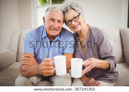 Portrait of senior couple sitting on sofa and having coffee in living room - stock photo