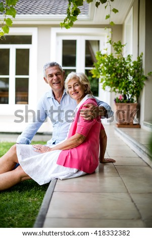 Portrait of senior couple sitting on steps outside house in yard - stock photo
