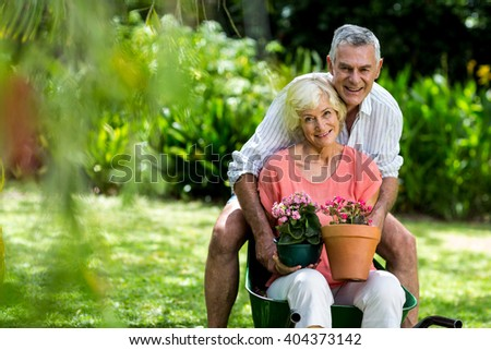 Portrait of senior couple with flower pots in yard - stock photo