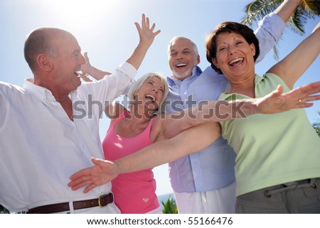 Portrait of senior couples smiling with arms up