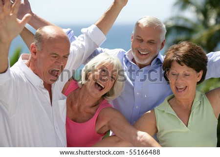 Portrait of senior couples smiling with arms up - stock photo