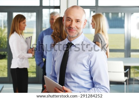Portrait of senior director holding hand digital tablet while standing at office building. Group of business people standing at background.  - stock photo