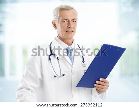 Portrait of senior doctor holding clipboard and checking patient list while standing at hospital. - stock photo