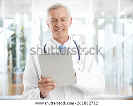 Portrait of senior doctor holding digital tablet and analyzing medical tests while standing at private clinic.