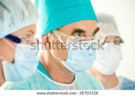 Portrait of senior doctor looking aside between two assistants - stock photo