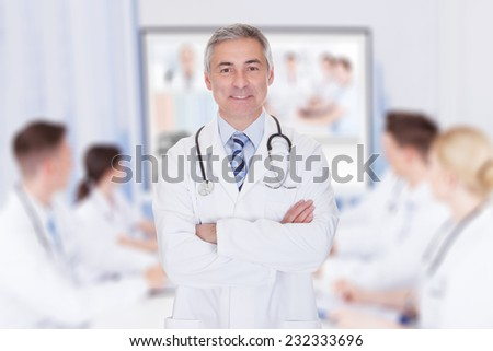 Portrait of senior doctor with arms crossed against team video conferencing in meeting room - stock photo