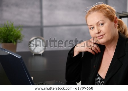 Portrait of senior executive businesswoman sitting at desk in office, looking at camera.