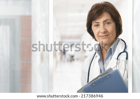 Portrait of senior female doctor standing at hospital corridor. - stock photo