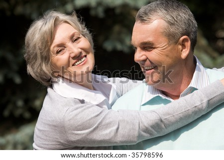 Portrait of senior female embracing her husband while he laughing - stock photo