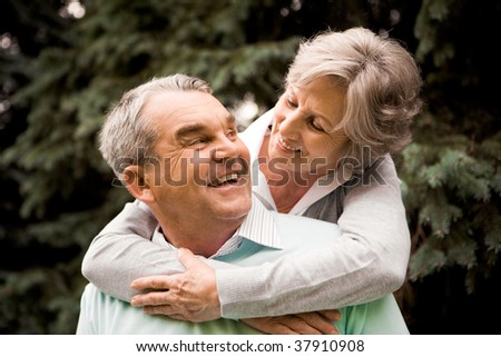 Portrait of senior female embracing her husband while he laughing and looking at her - stock photo