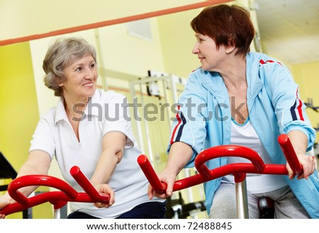 Portrait of senior females doing physical exercise on special equipment in gym - stock photo