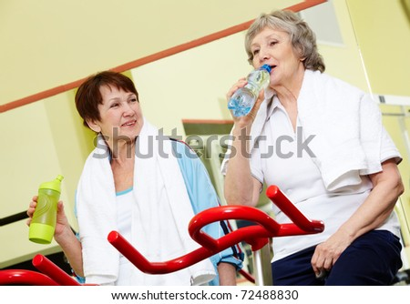 Portrait of senior females refreshing after workout in gym - stock photo