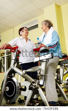 Portrait of senior females refreshing and chatting after workout in gym - stock photo