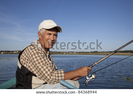 Portrait of senior fisherman with fishing rod in his hands - stock photo