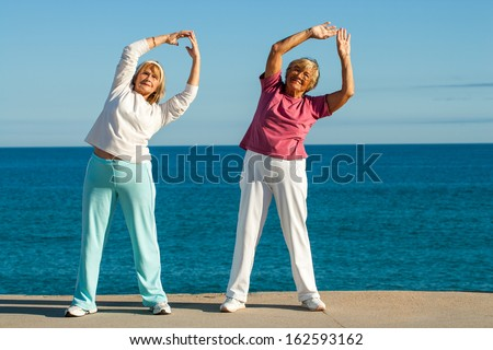 Portrait of senior fitness ladies stretching arms together at seafront.