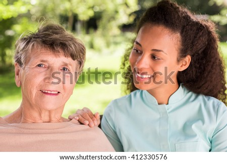 Portrait of senior happy woman and her young caregiver