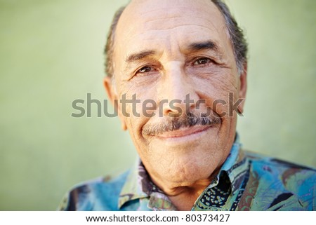 portrait of senior hispanic man with mustache looking at camera against green wall and smiling. Horizontal shape, copy space