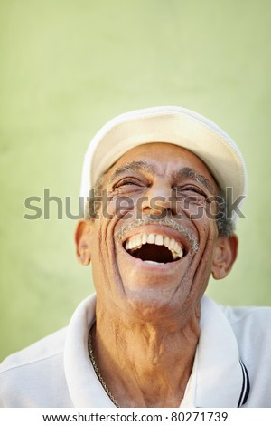portrait of senior hispanic man with white hat looking up against green wall and smiling. Vertical shape, copy space - stock photo