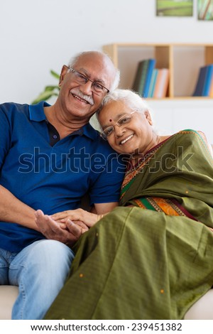 Portrait of senior Indian couple smiling and looking at the camera - stock photo