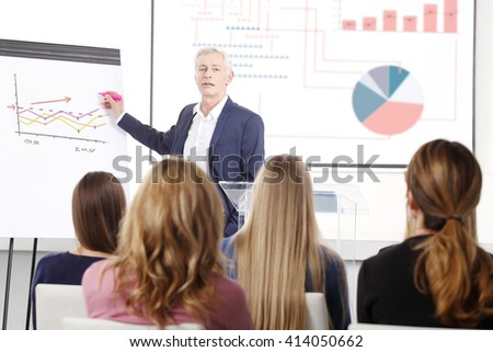 Portrait of senior investment professional man giving presentation to the group of business people at conference.