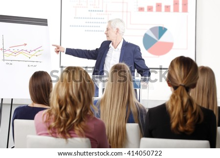Portrait of senior investment professional man giving presentation to the group of business people at conference. - stock photo