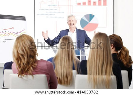 Portrait of senior investment professional man giving speech to the group of business people at conference.