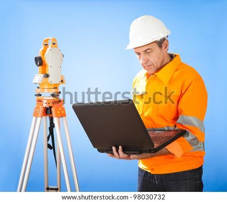 Portrait of Senior land surveyor working with theodolite at construction site - stock photo