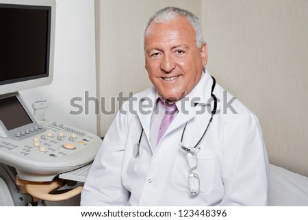 Portrait of senior male radiologist smiling with ultrasonic machine in background - stock photo