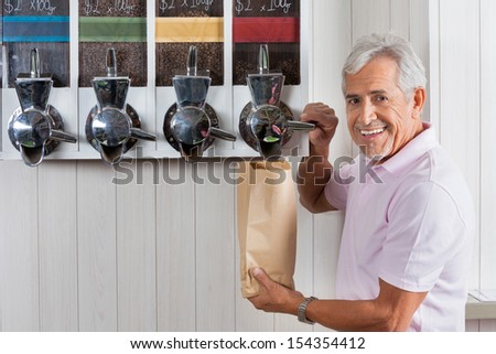 Portrait of senior man buying coffee beans from vending machine at grocery store - stock photo