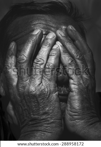 portrait of senior man covering his face with his hands. black and white image  - stock photo