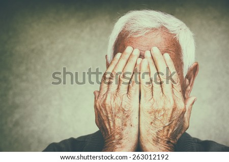 portrait of senior man covering his face with his hands. retro filtered image - stock photo