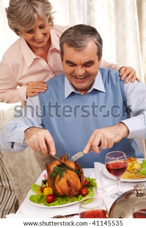 Portrait of senior man cutting roasted turkey with his happy wife behind - stock photo